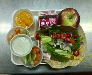 tray with carrot & celery sticks with dressing, apple, peaches, milk, chicken wrap topped with fresh veggies