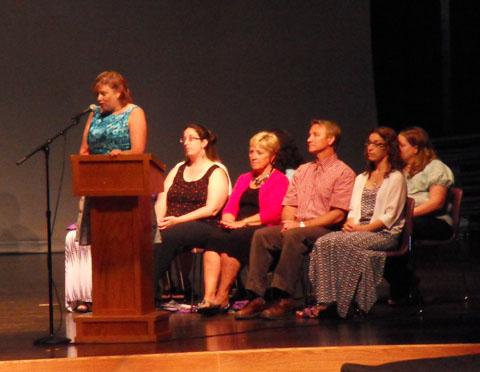 Principal Lent addresses the audience as teachers listen