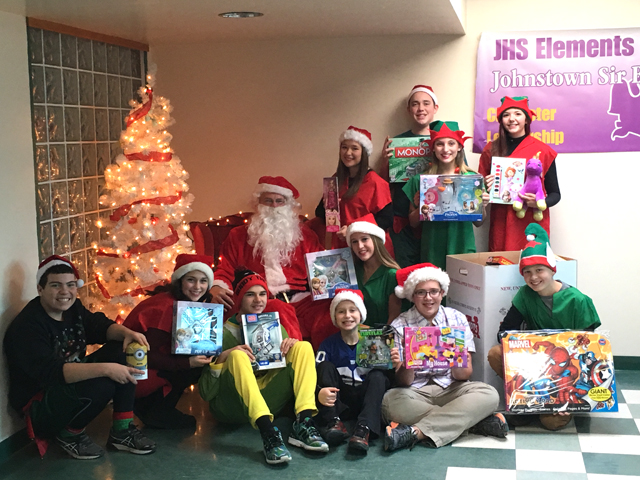 Class members pose by tree with Santa and toys