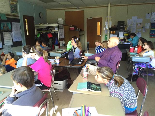 Mr Ettington sits at desks among students