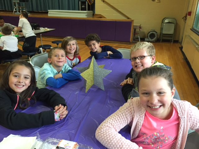 six students sit around table with purple tablecloth and star in the middle