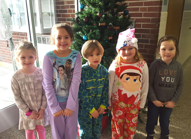 five students stand in a row in front of Christmas tree