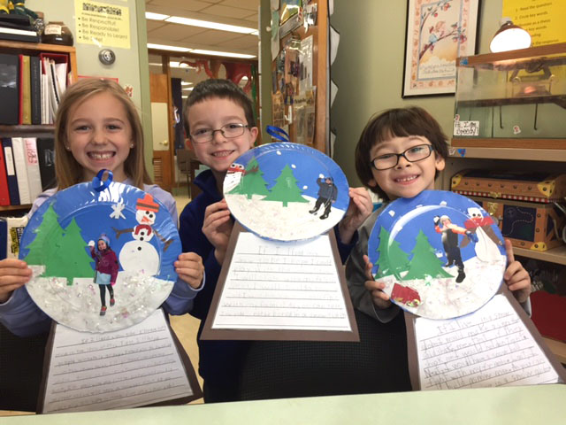 three students hold up plates decorated like snow globes with stories stapled to base
