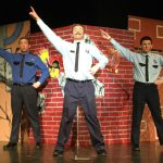 three performers dressed as policeman sing on stage