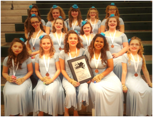 jv winter guard sits on bleachers in costume with their plaque