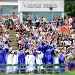 graduates stand and face the crowd