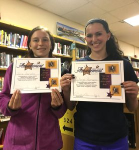 Julia Sarullo and Kathryn Romano holding certificates while standing in library