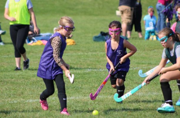 girls run to ball with field hockey sticks in hand
