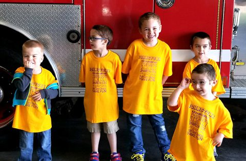 five boys stand by firetruck