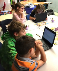 two boys look at a Chromebook