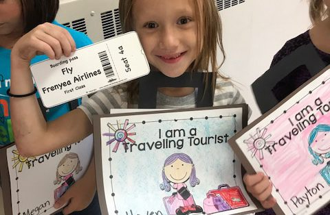 """girl holds up her """"Frenyea Airlines"""" ticket"""