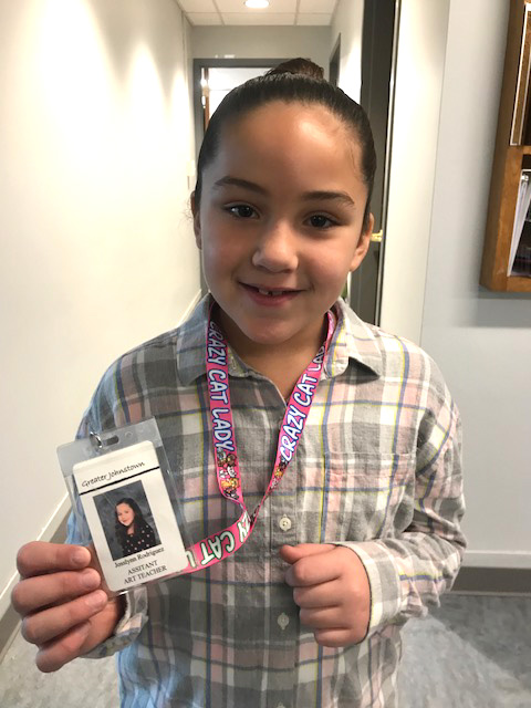 girl holding badge with title art assistant