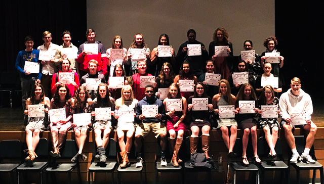 group photo of student athletes on lecture hall stage