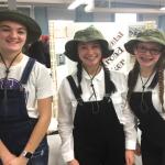 three girls dressed as railroad workers