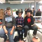 three boys sitting on table, two in cowboy hats
