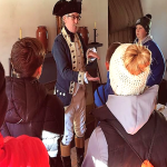 man in historical garb talks to students
