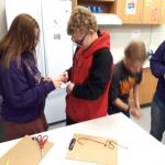 girl helps boy with bracelet