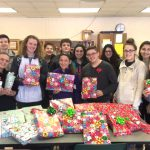 group poses with wrapped presents