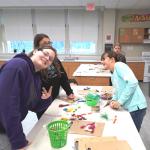 three girls at table full of craft materials