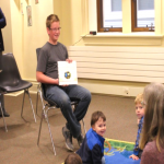 boy reading to kids at library