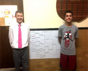 two boys stand in front of tournament bracket chart