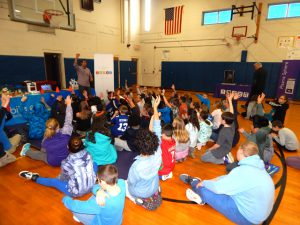 students sit on gym floor and raise hands to ask questions