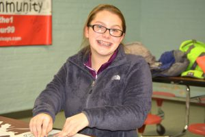 girl with glasses smiles at camera