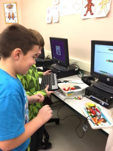 two boys build with legos from plan on computer screen