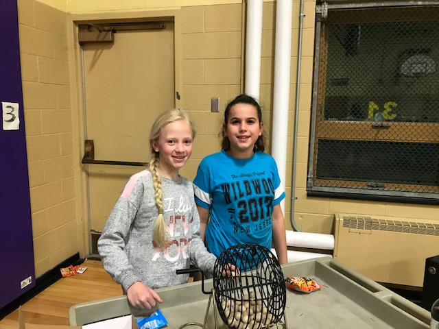 two girls spin and draw from the numbers basket