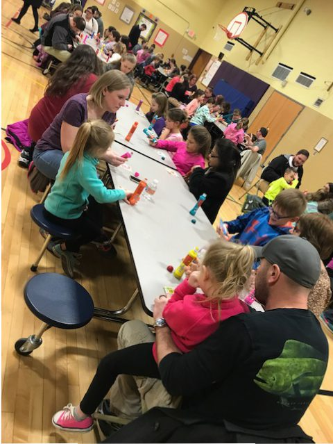 parents and children playing BINGO with markers