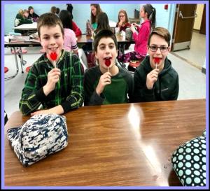 three boys with heart lollipops