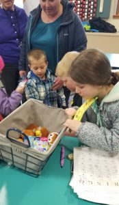 kids looking at toys in a bin