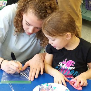 high school girl and elementary student work together