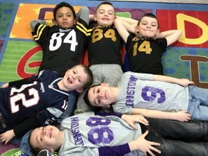 students wearing various shirts and jerseys with numbers lay on the floor