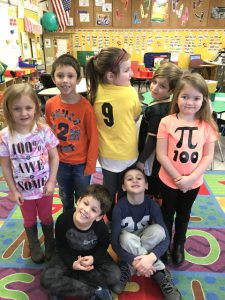 group of students wearing shirts with numbers and Pi symbols