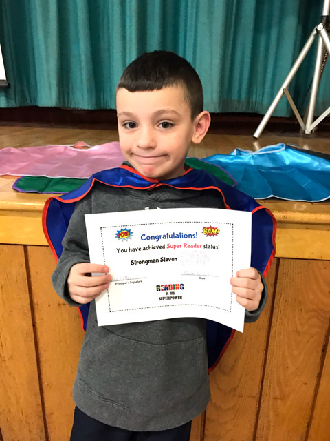 boy with certificate and cape