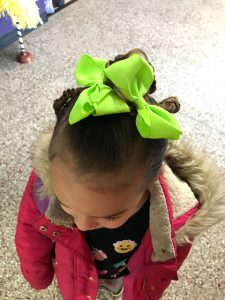 girl with big green bows and a braid