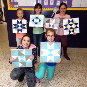 five students pose with quilt squares