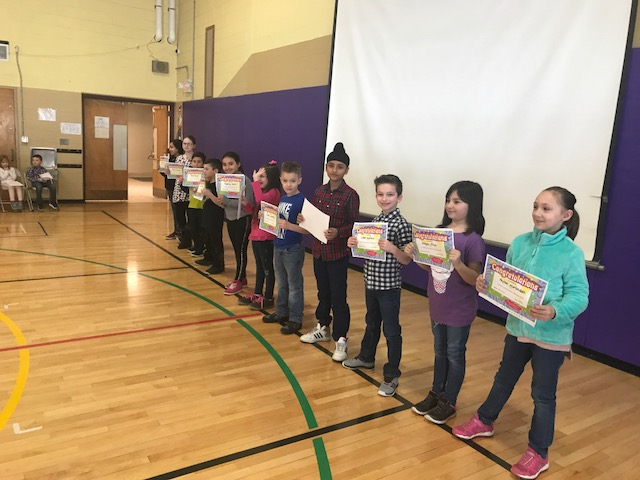 Soar for 4 Students of the Month line up in gymnasium