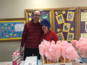two adults stand behind table with cotton candy