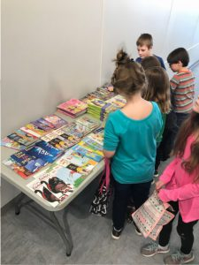 kids peruse a table of books