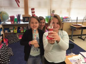 two girls hold up craft projects
