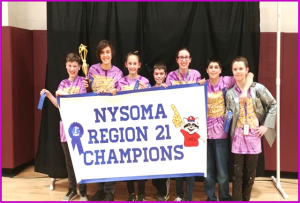 Odyssey of the Mind group posing with Region 21 Champions banner