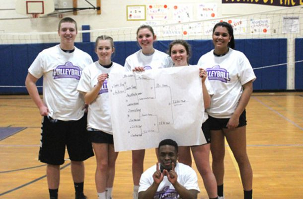 winning student volleyball team poses in the gym
