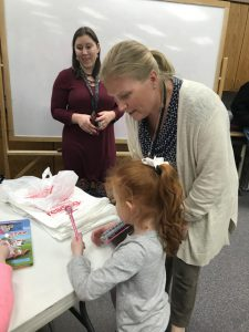 Principal Cotter and girl look at books on table