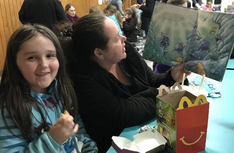 mother holding book, girl eating McDonald's Happy Meal