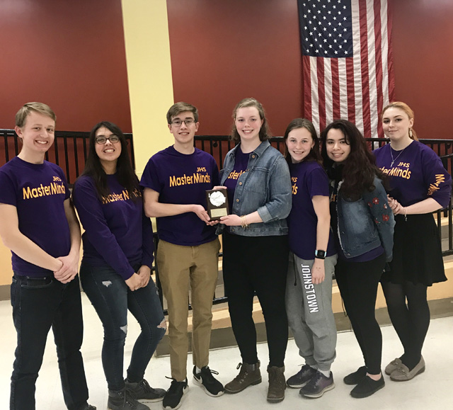 students pose for group photo holding small plaque