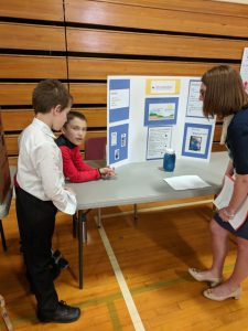 students talking to a judge about their project
