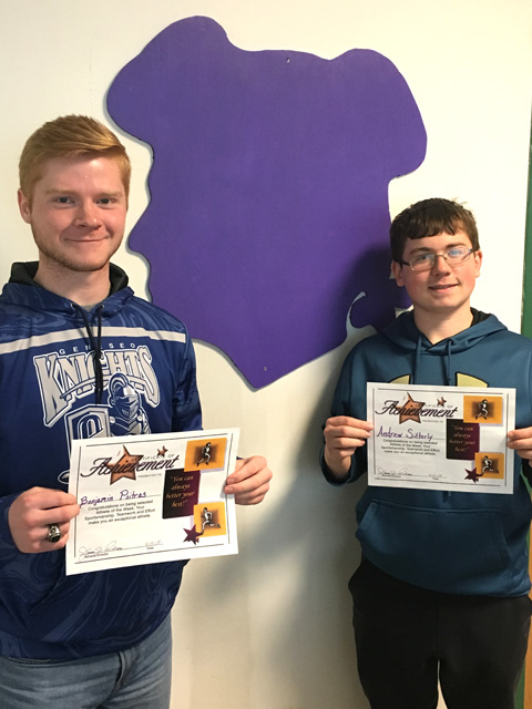 boys with certificates stand next to wall with Sir Bills outline