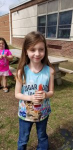 little girl standing by picnic table